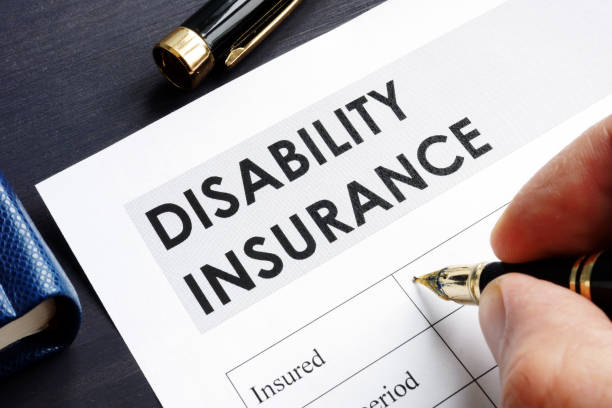 Man is filling in Disability insurance form. stock photo