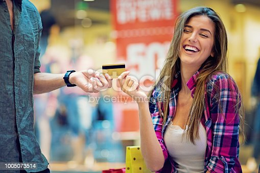 Man is giving credit card to his girlfriend in the Mall