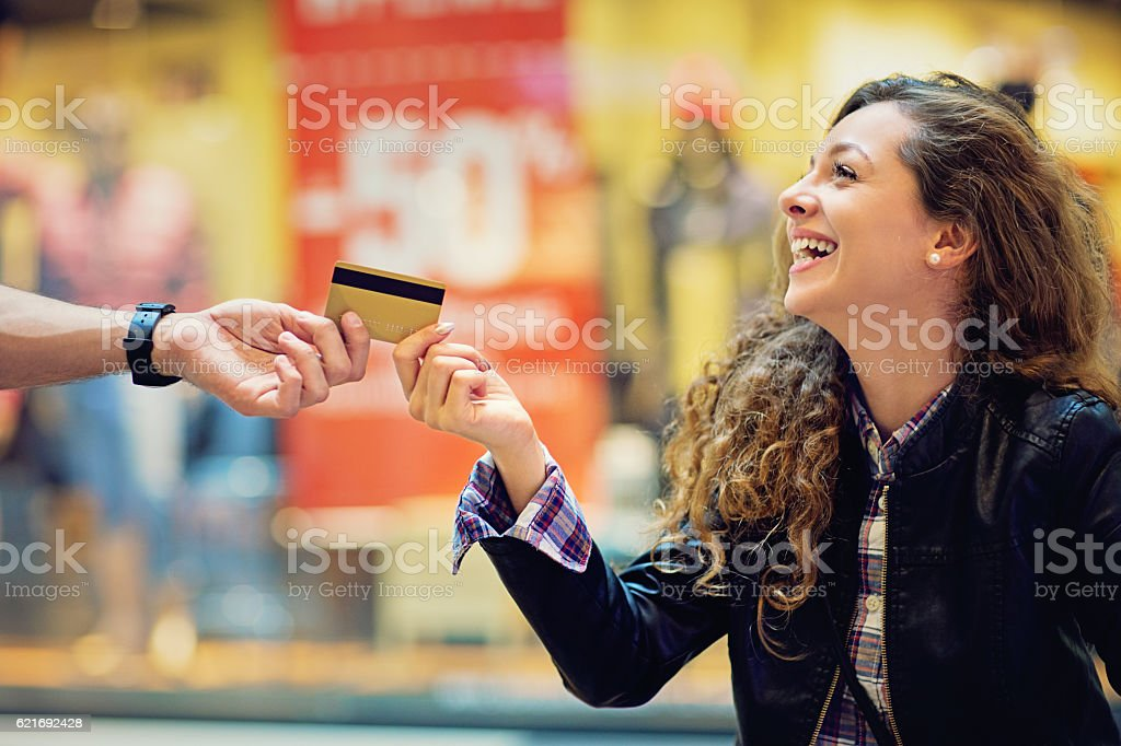 Man is giving credit card to his girlfriend stock photo