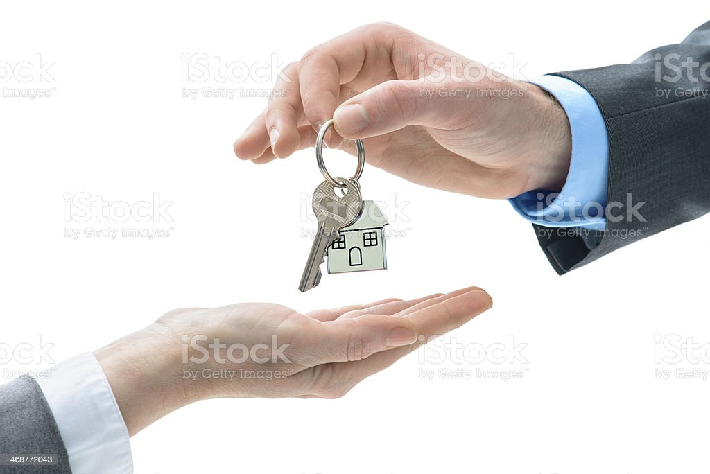 Man is handing a house key to other hands royalty-free stock photo