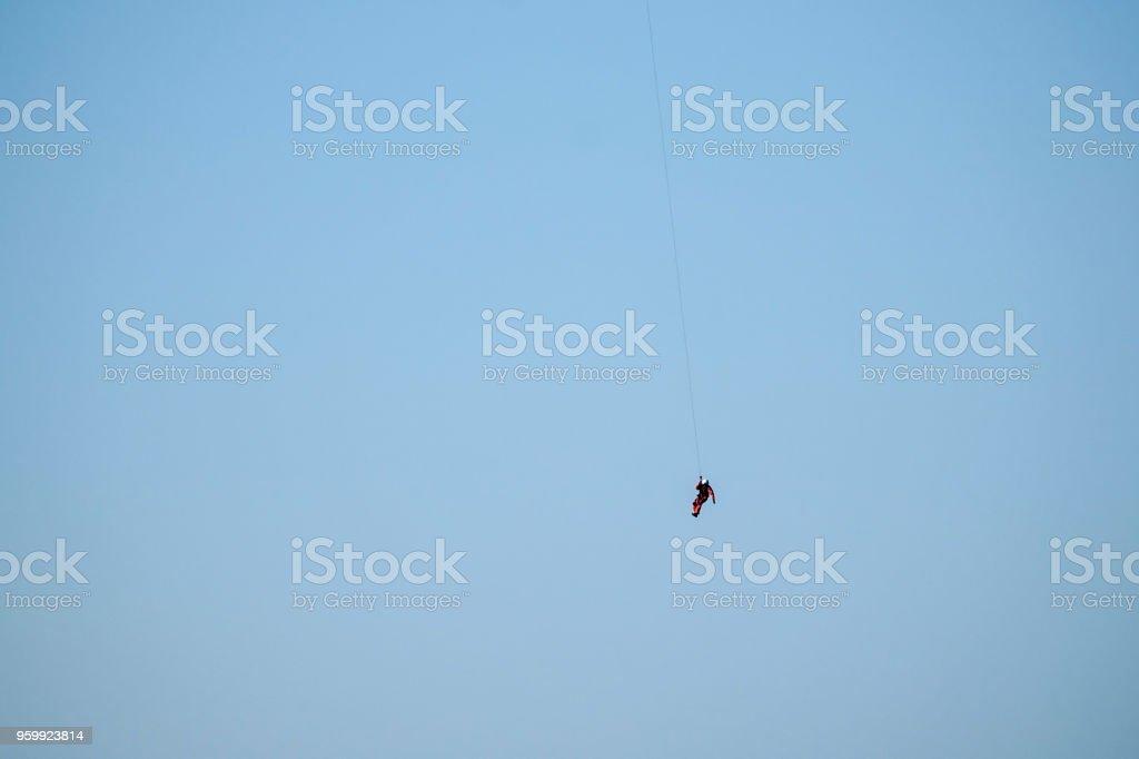 Um homem está pendurado por um helicóptero no céu - foto de acervo