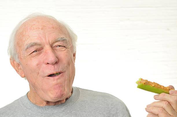 man is happy eating celery and peanutbutter - peanutbutter bildbanksfoton och bilder