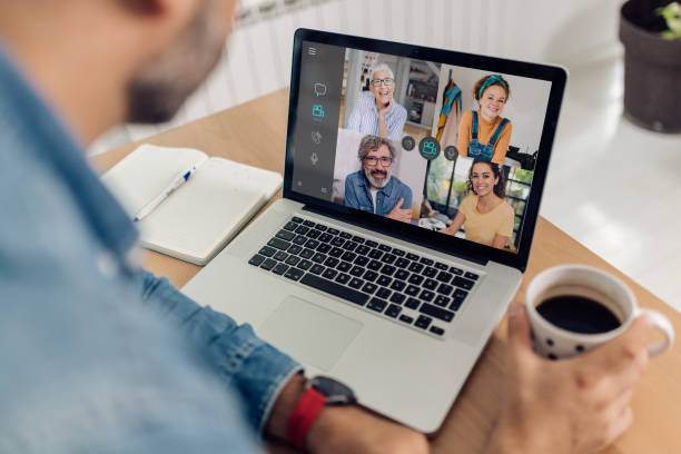 Man is having an online meeting with his coworkers stock photo