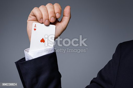 Gambling addiction concept. Man is hiding an Ace card in the sleeve.