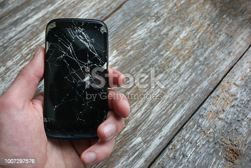 istock Man is holding a crashed black smartphone in hand on the wooden background. Broken lcd touch screen. Information technology photo. 1007297576