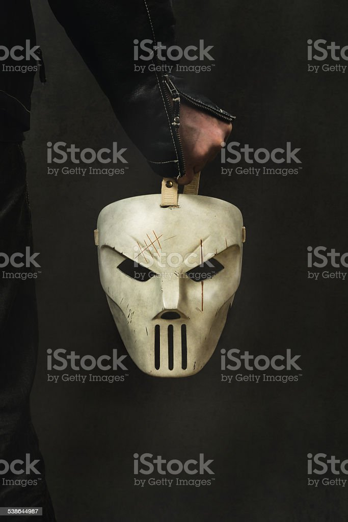 man is holding a creepy Mask stock photo