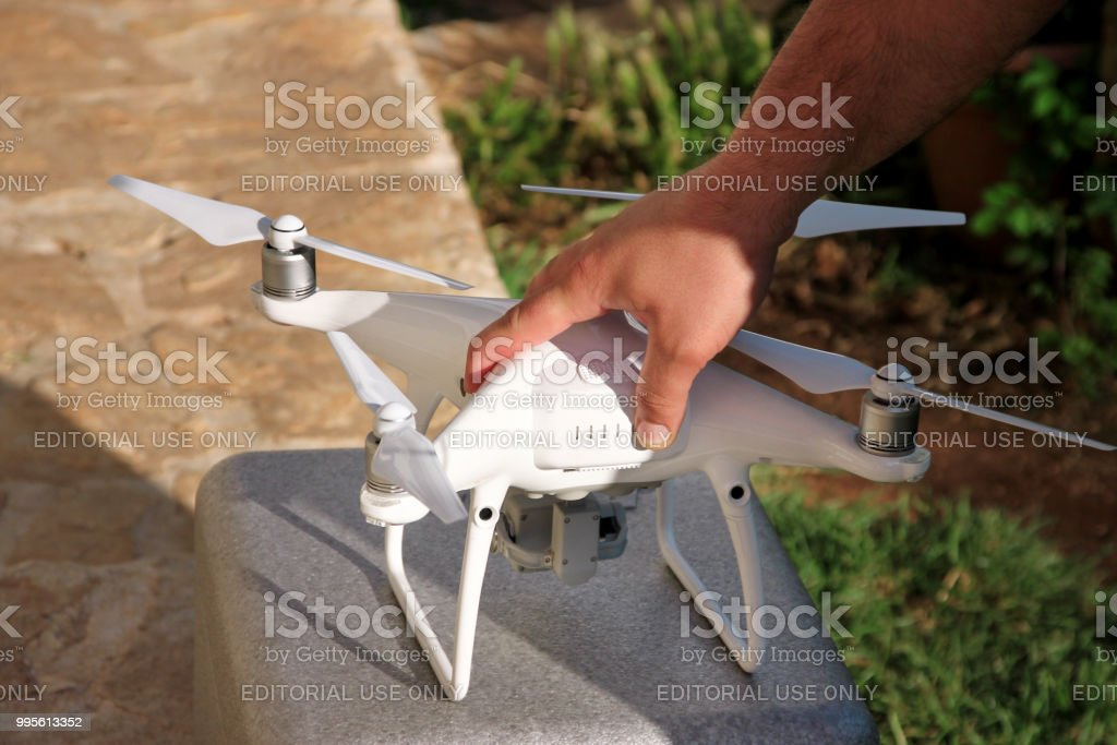 Homem está segurando um zangão na mão. Mãos de homem branco quad helicóptero Drone e fotógrafo. Piloto profissional possui painel de controle remoto com tela e controles. - foto de acervo