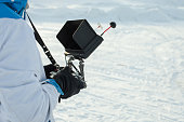 man is holding a professional remote control from a quadrocopter against the background of a snow field