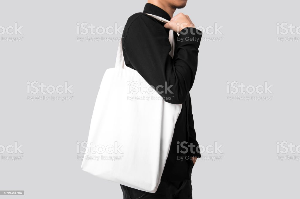 Man is holding bag canvas fabric for mockup blank template isolated on gray background. stock photo