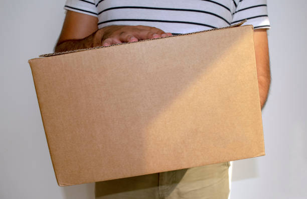 Man is holding big cardboard box delivery parcel. stock photo
