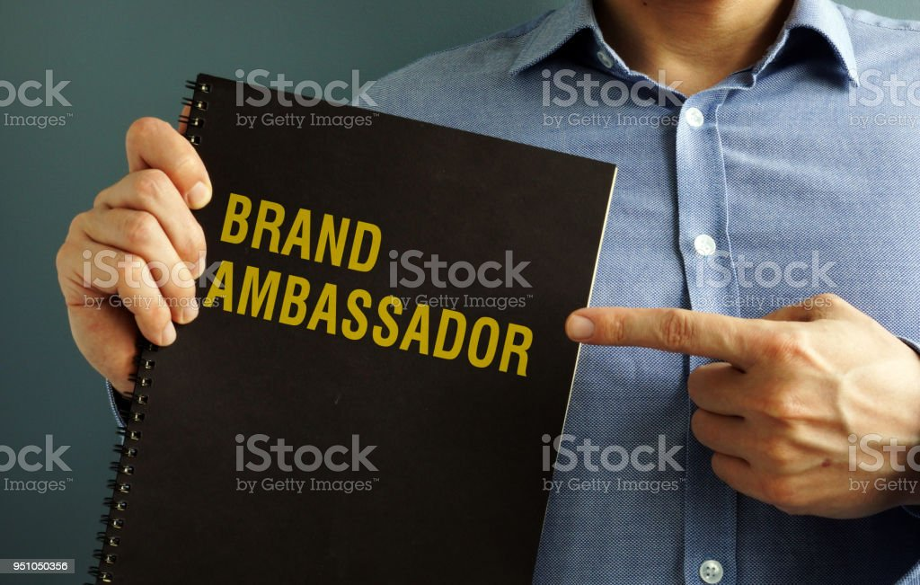 Man is holding book with title Brand Ambassador. stock photo