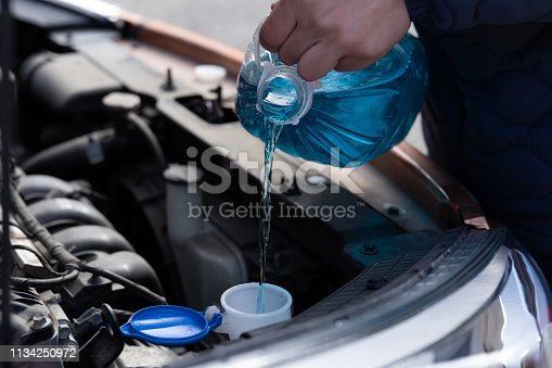 istock Man is holding bottle of blue antifreeze in hands and pouring antifreeze liquid for washing car screen 1134250972
