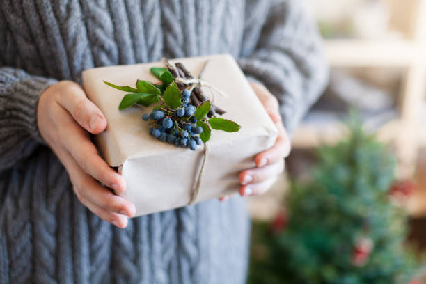 Man is holding gift near Christmas tree. Boy gives box present. Blue decorating in rustic style with kraft paper, natural materials, berries, holly. Guy is wearing in woolen gray knitted sweater. stock photo