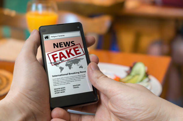 Man is holding smartphone and reading fake news on internet. Propaganda, disinformation and hoax concept. stock photo