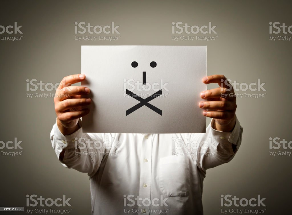 Man is holding white paper with smile. Lips sealed and silence concept. stock photo