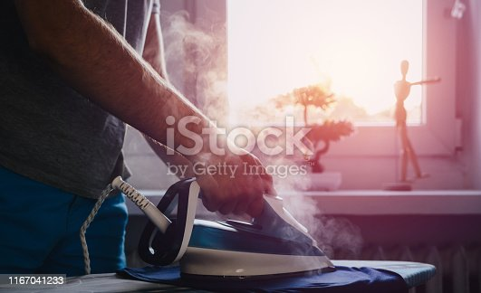 istock Man is ironing clothes. The concept of caring for the home, helping men in household chores. 1167041233
