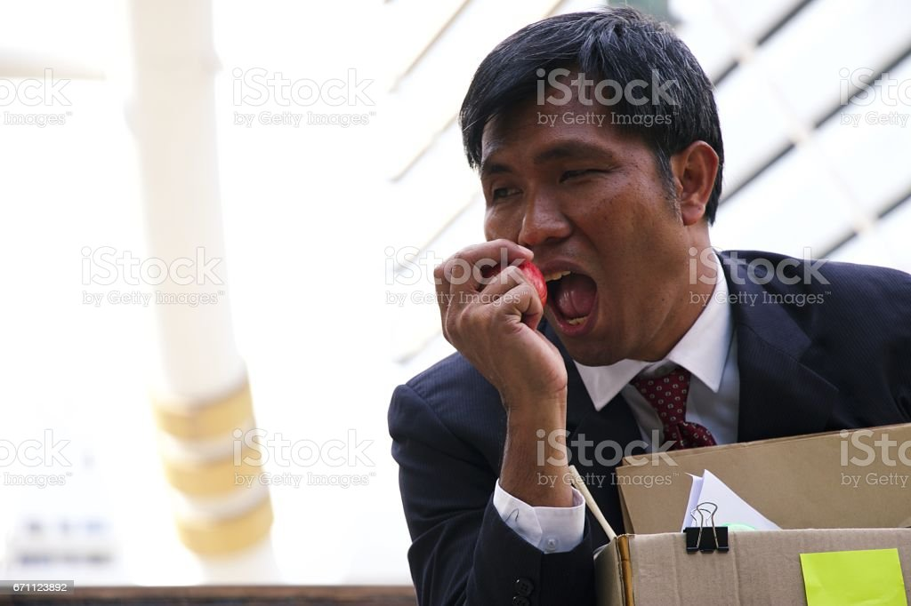 Man is just laid off. He is stressed and hopeless. He packed his stuff and sits at stairs at the station. stock photo