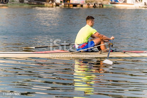 Photo of Handsome Young Man who is Rowing a Kayak in a Lake. Sportsman in Canoe is Preparing for Competition on River on Sunny Summer Day. Sports, Competition and Challenge Concept.