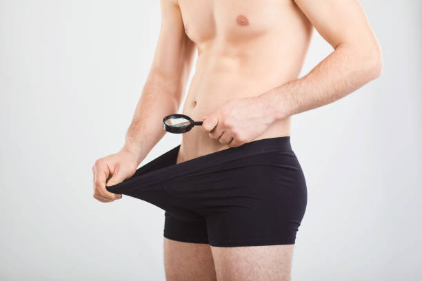A man is looking at a penis with his magnifying glass. stock photo