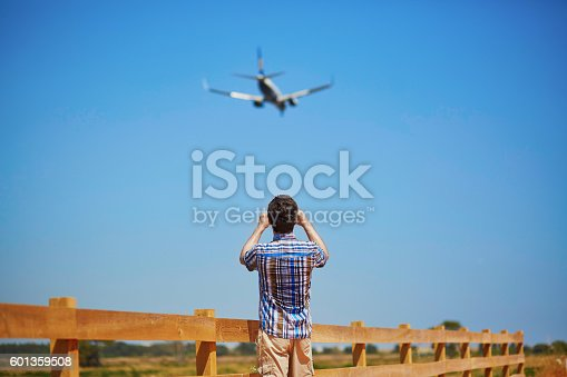 istock Man is looking at the glide path and landing plane 601359508
