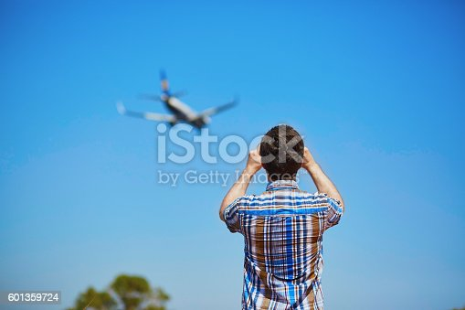 istock Man is looking at the glide path and landing plane 601359724
