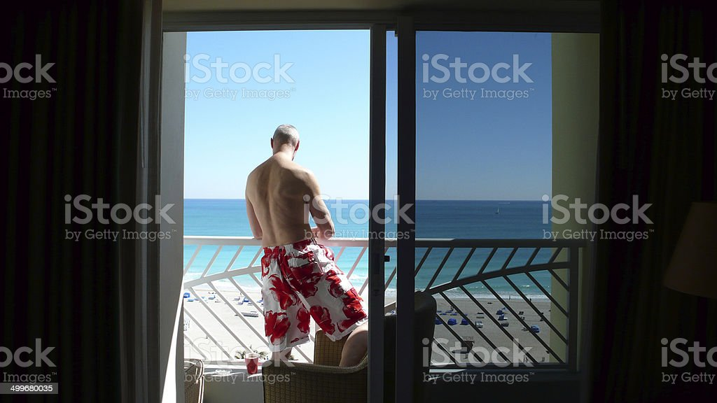 Man is looking downwards from balkony at Beach of Miami stock photo