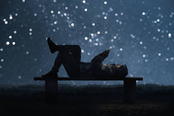 Man is lying on a bench and using a smartphone starry sky bokeh in picture id1039635412?b=1&k=6&m=1039635412&s=612x612&w=0&h=owsfpitjlc4gl0 eweea0pu6wtfxwiluurfpfbpnfl8=
