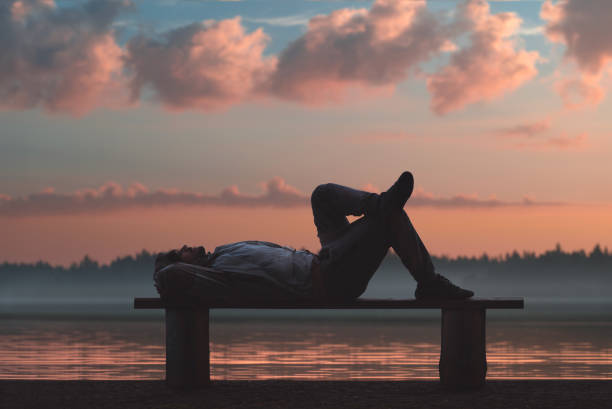 a man is lying on a wooden bench in a picturesque place. lake and forest in the background. - mani dietro la testa foto e immagini stock