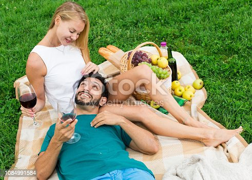 Man is lying on the lap of girlfriend in time picnic in the park.