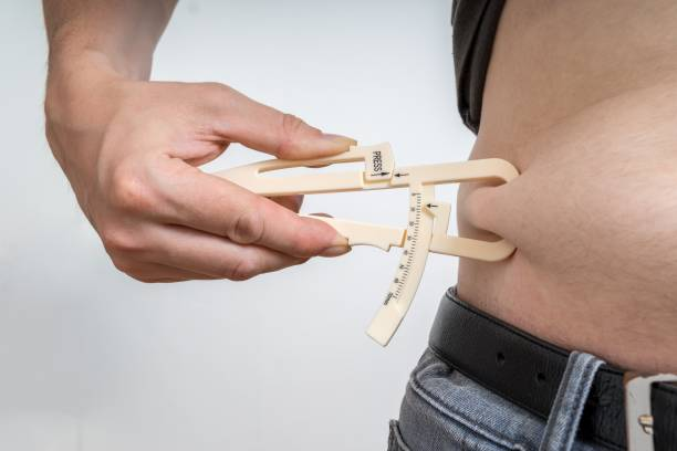Man is measuring body fat on his belly with caliper. stock photo