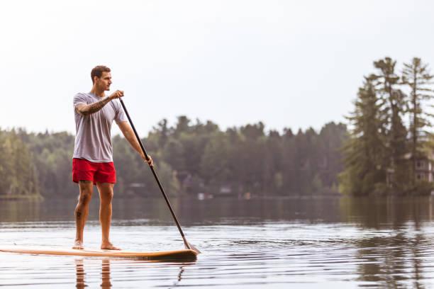 ein mann ist paddling und rudern auf einem see. sup stand up paddleboard. mauricie, quebec, kanada - stehpaddeln stock-fotos und bilder