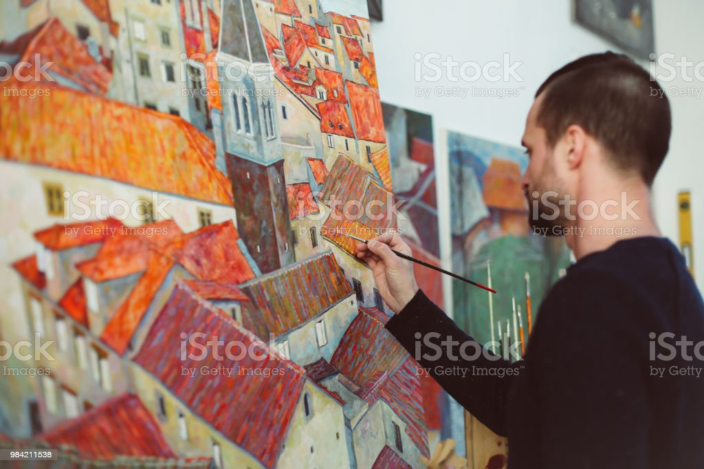 Side view of man painting houses with colorful roofs