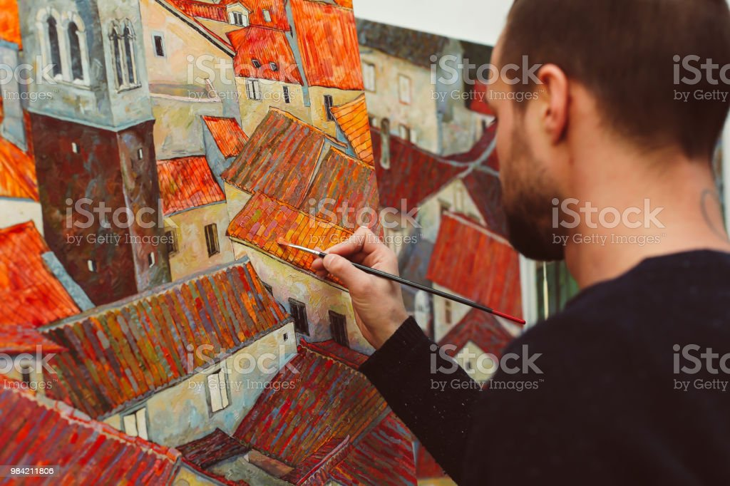 Side back view of man painting houses with colorful roofs