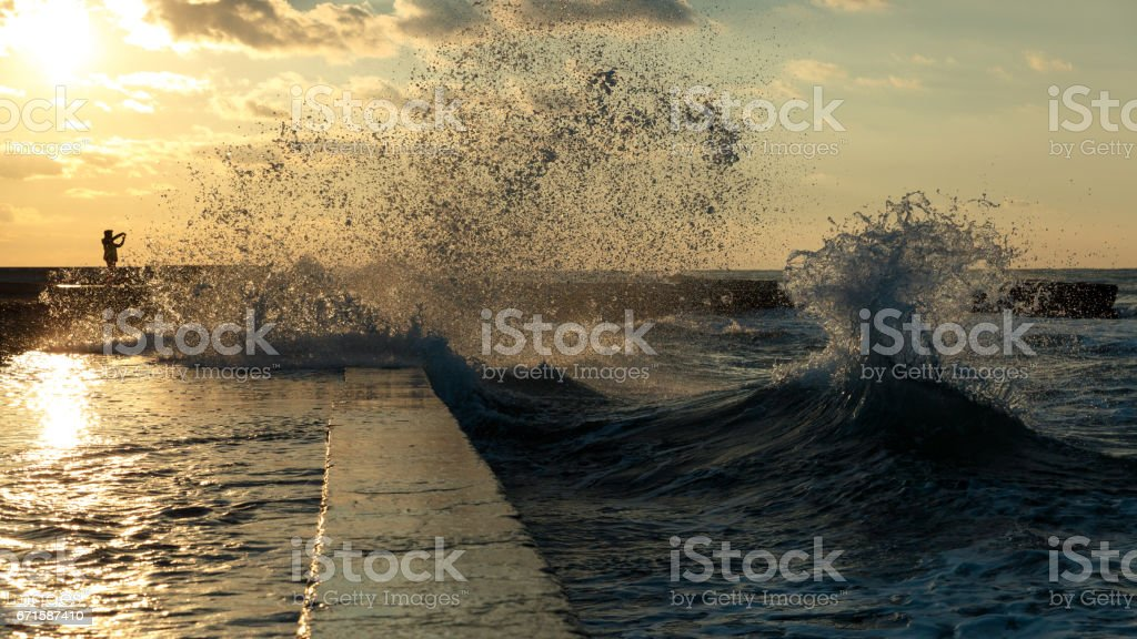 A man is photographing a sea storm. Seascape on sunset background stock photo