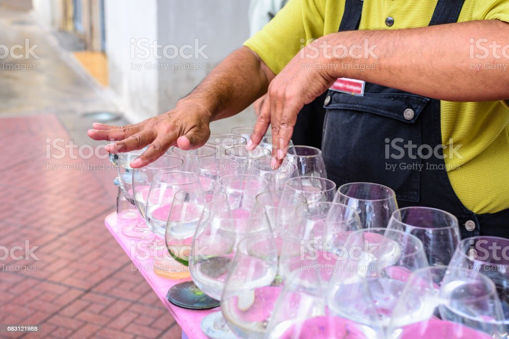 Man is playing a glass harp. stock photo