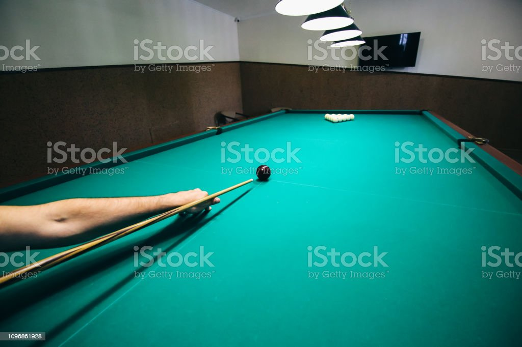 Man is playing billiard. Guy is holding pool cue in his hand. Small...
