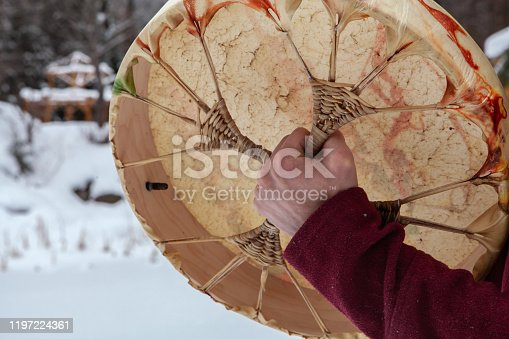 Young man wearing a red shirt is pictured from the back is playing his sacred drum with a drumstick. Pictured from the back, outside in winter