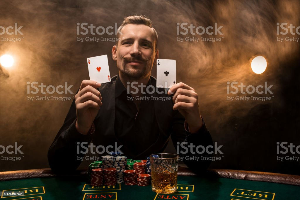 Man is playing poker with a cigar and a whiskey, a man show two cards...