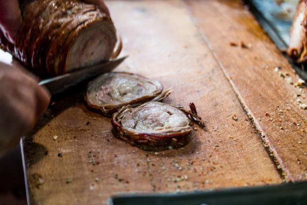 man förbereder kokorec (stekt får tarm) med kniv på träytan. - kokoreç bildbanksfoton och bilder