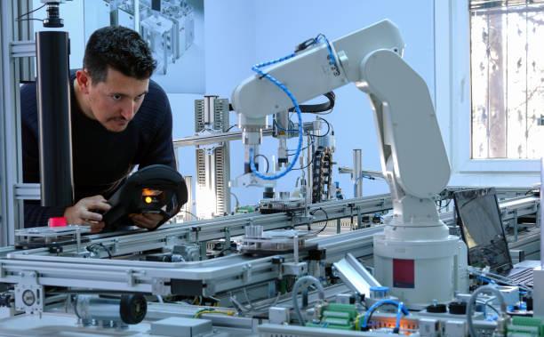 el hombre está programando brazo robótico - robótica fotografías e imágenes de stock