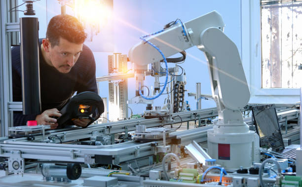 el hombre está programando el brazo robótico con el panel de control que está integrado en la línea de producción de fábrica inteligente. línea de automatización de la industria 4.0 que está equipada con sensores y brazo robótico - robótica fotografías e imágenes de stock