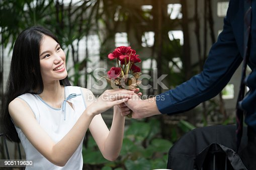 1129577106 istock photo A man is proposing marriage to a smiling woman with a lovely flower bouquet in a beautiful garden, lover and couple concept, surprising proposal 905119630
