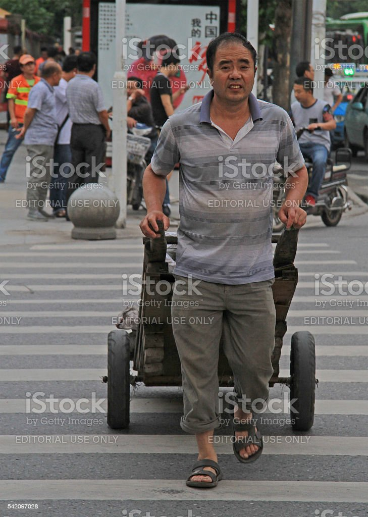 man is pulling a cart outdoor in Wuhan, China stock photo