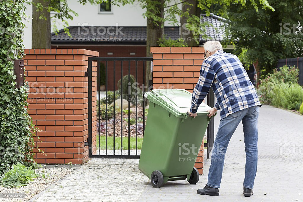 Man is pushing wheeled dumpster stock photo