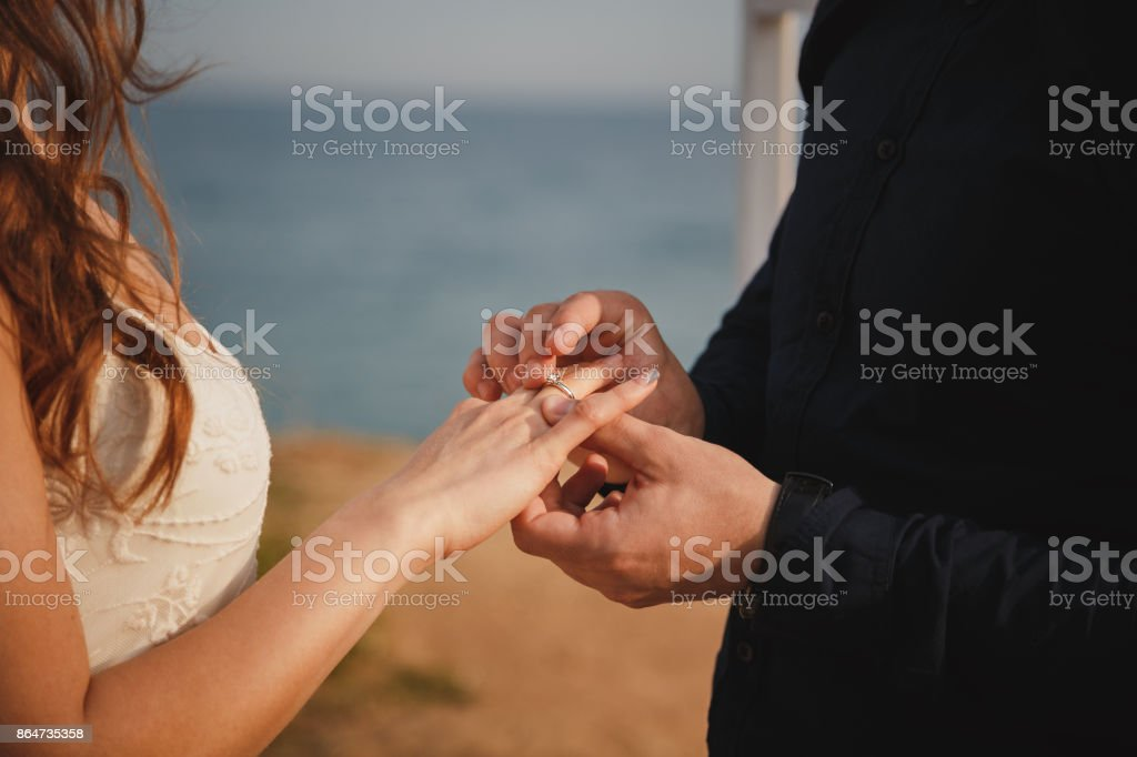 Man is putting wedding ring on his bride's hand, close up. Outdoor beach wedding ceremony, stylish groom and bride are standing near wedding altar on the sea shore stock photo