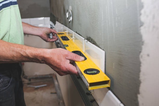 man is putting white tiles on the grey concrete. maintenance repair works renovation in the flat. restoration with bubble level indoors. work in process. man is holding a spirit level in hands. - bathroom renovation stock photos and pictures