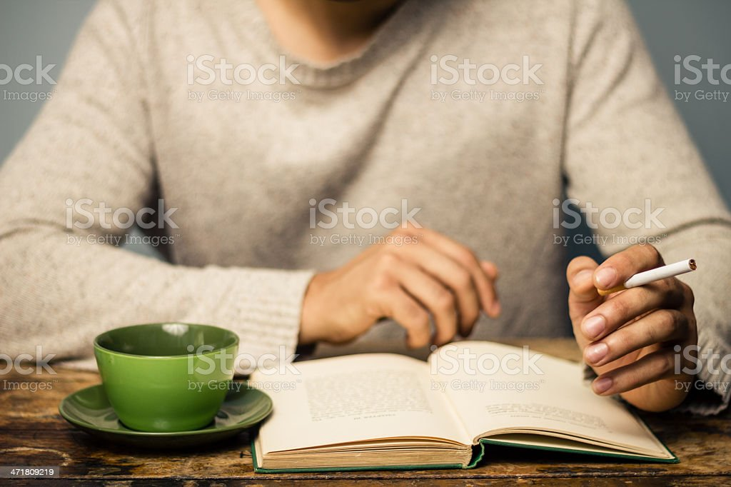 Man is reading and smoking in cafe royalty-free stock photo