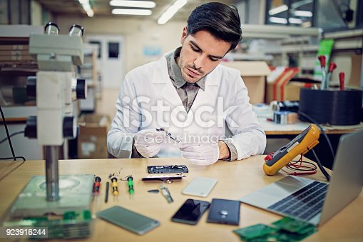 Man is repairing a mobile phone in the service