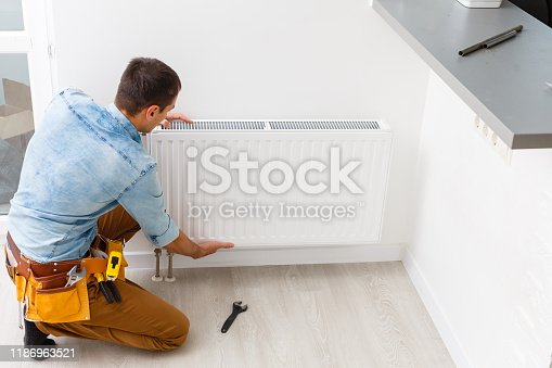 Man is repairing radiator battery in the room. Maintenance repair works renovation in the flat. Heating restoration. Wrench in hands.