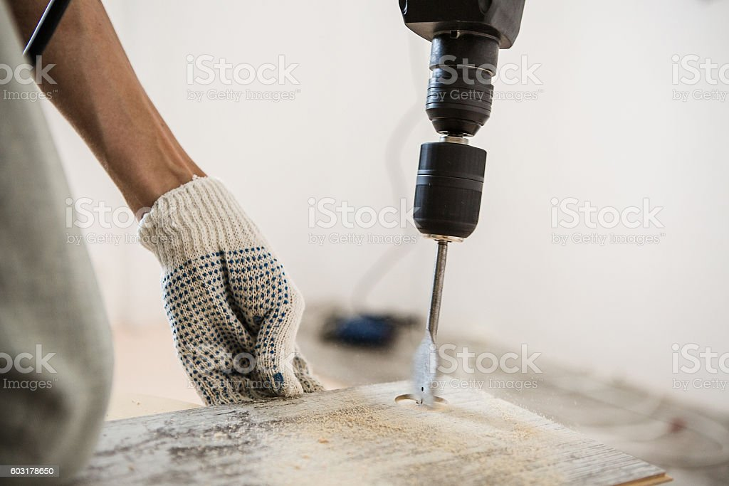man is repairing the floor in the house stock photo
